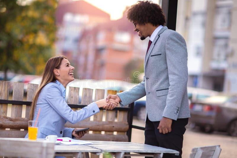 Femme d'affaires et poignée de main d'homme d'affaires dans le café photographie stock