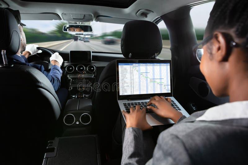 Femme d'affaires Examining Gantt Chart tout en voyageant en voiture photographie stock