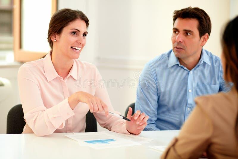 Femme d'affaires expliquant aux collègues une idée images stock