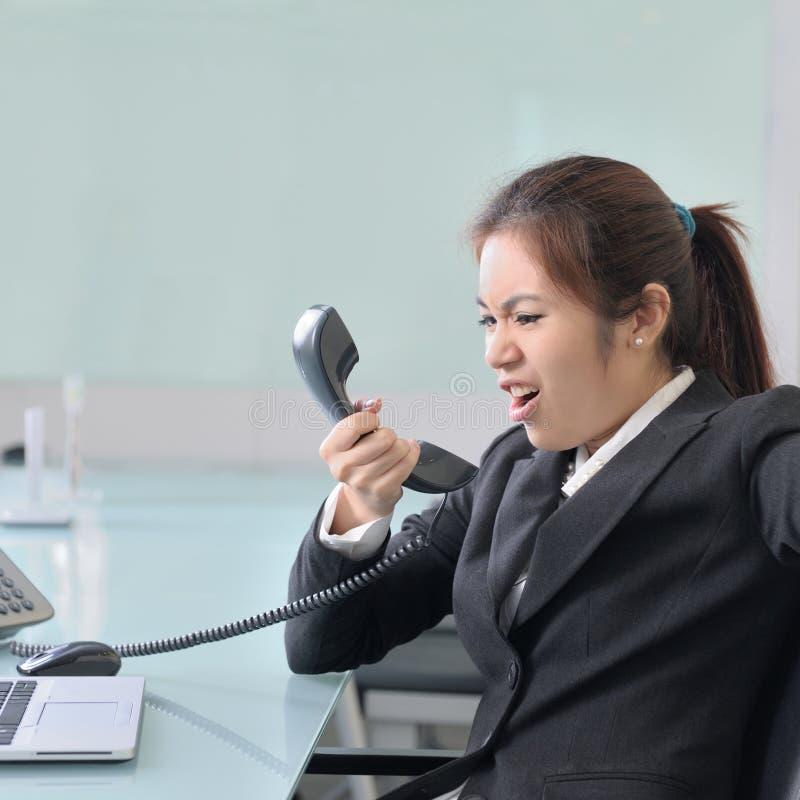 Femme d'affaires fâchée avec le téléphone image stock