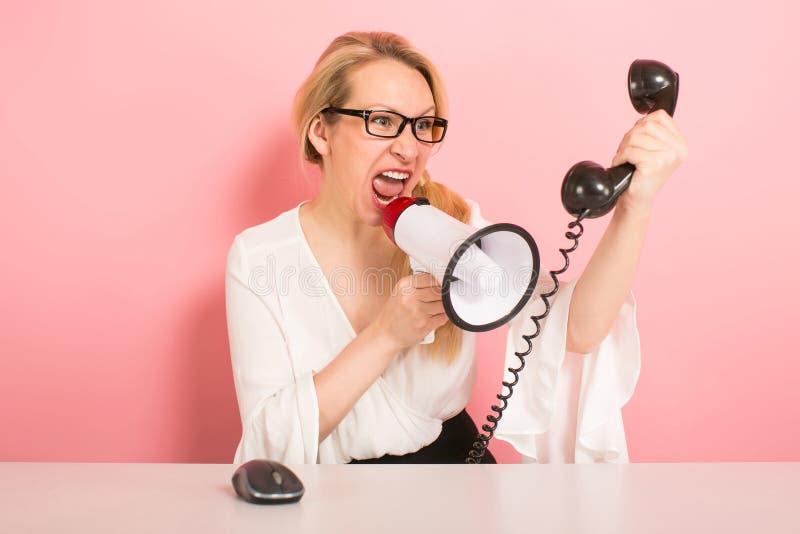 Femme d'affaires fâchée avec le téléphone et le haut-parleur photographie stock