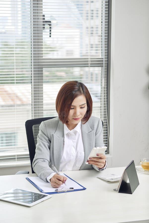 Femme d'affaires faisant des notes regardant un téléphone portable le bureau images stock