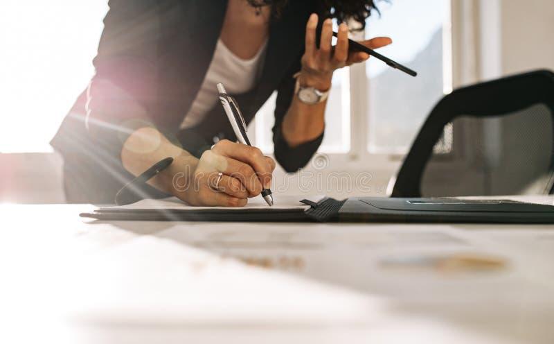 Femme d'affaires faisant des notes se tenant à son bureau dans le bureau photographie stock libre de droits