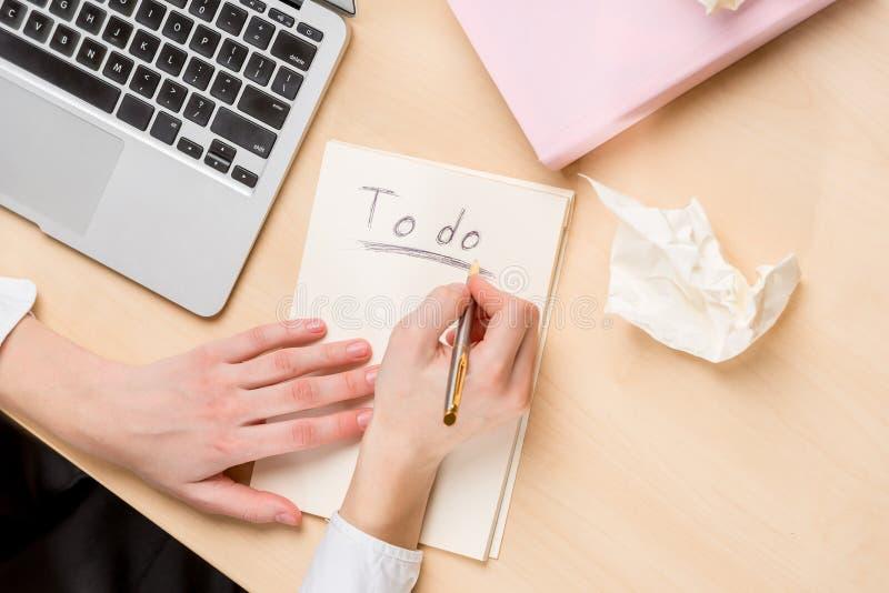 femme d'affaires faisant les notes dans un carnet, vue supérieure sur le deskto photo stock