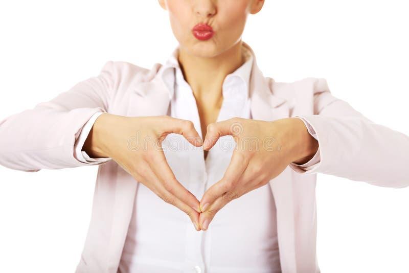 Femme d'affaires faisant une forme de coeur avec ses mains image libre de droits