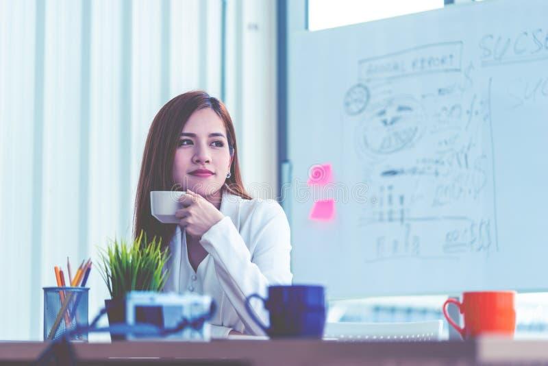 Femme d'affaires faisant une pause dans le bureau détendant avec du café images stock