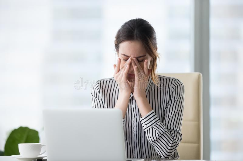 Femme d'affaires fatiguée massant le mal de tête de fatigue de tension de sentiment de yeux soulageant la douleur photos stock