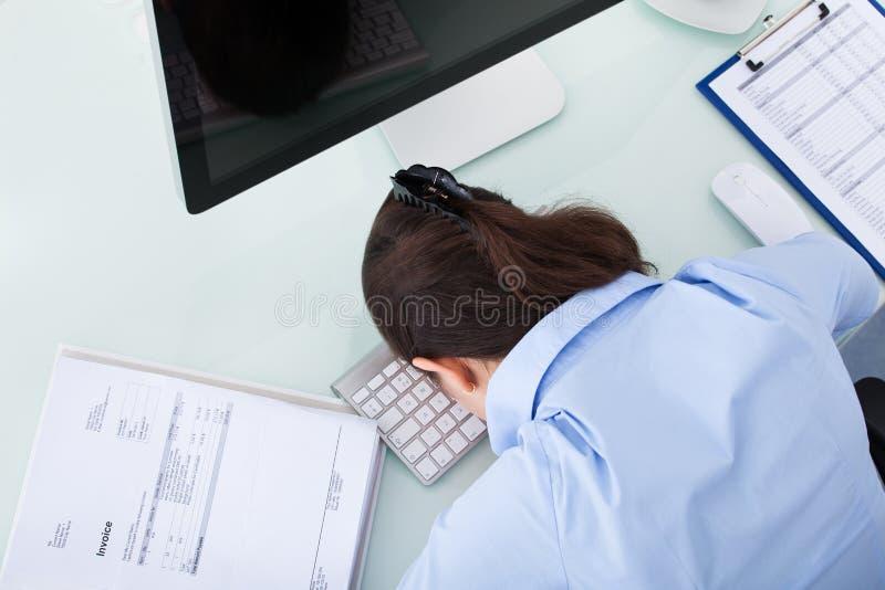 Femme d'affaires fatiguée se penchant au bureau photo stock