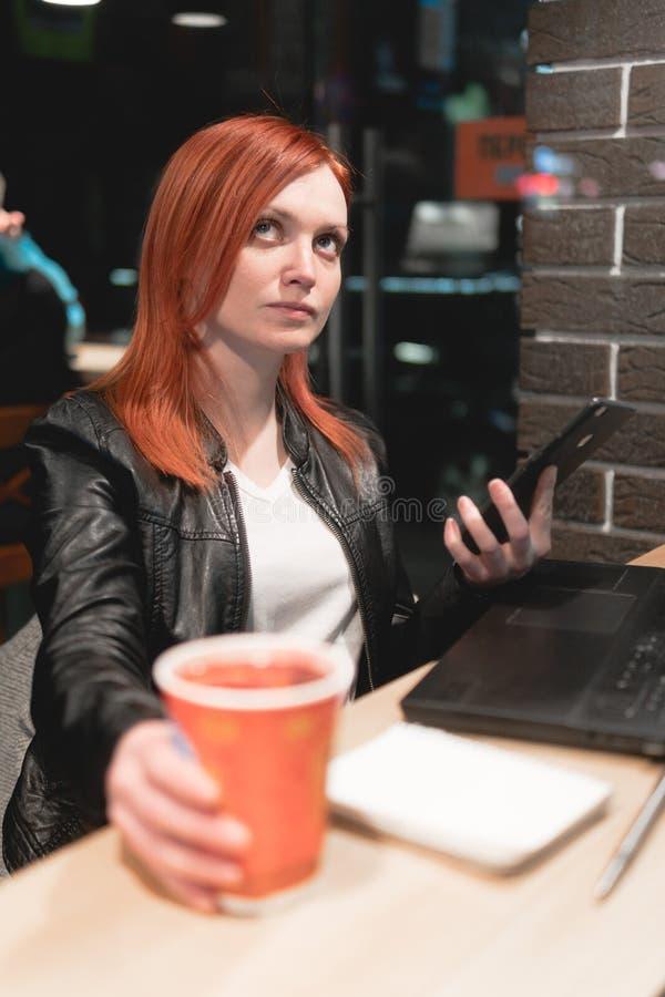 Femme d'affaires, fille travaillant sur l'ordinateur portable en caf?, smartphone de prise dans des mains, stylo, t?l?phone d'uti images libres de droits
