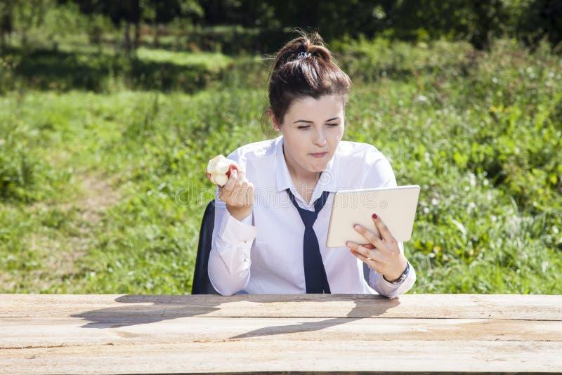 Femme d'affaires focalisée mangeant une pomme et lisant des messages photo stock