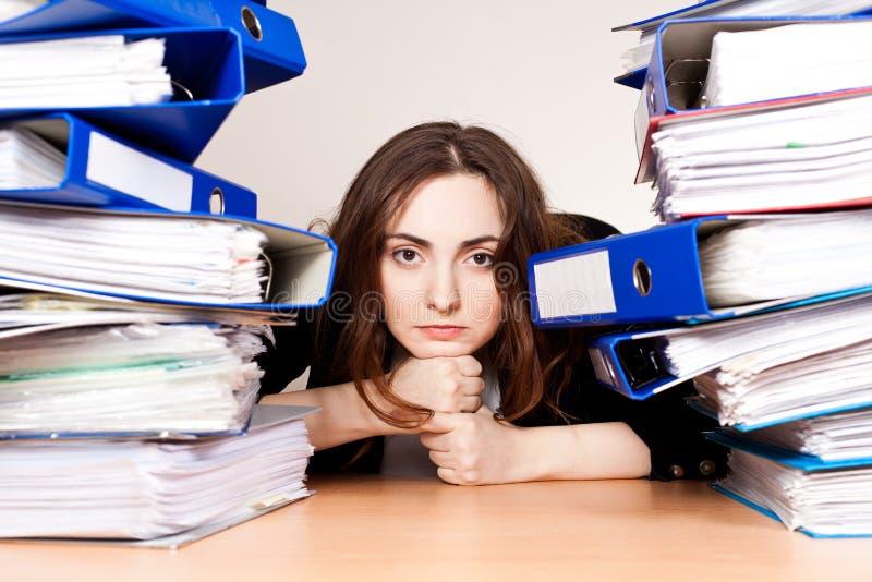 Femme d'affaires frustrante avec la pile de dépliants photos stock