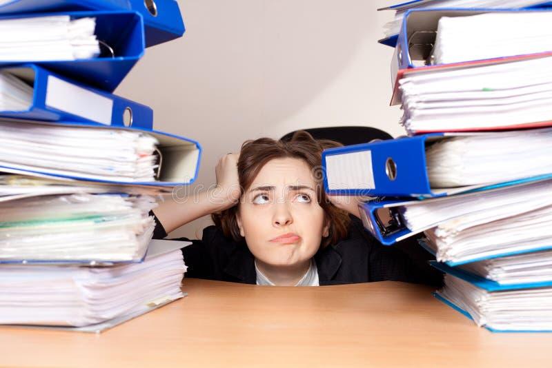 Femme d'affaires frustrante avec la pile de dossiers au bureau images stock