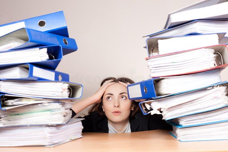 Femme d'affaires frustrante avec la pile de dossiers au bureau photos stock