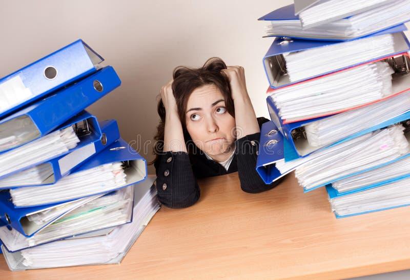 Femme d'affaires frustrante avec la pile de dossiers au bureau image libre de droits