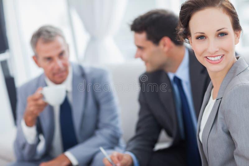 Femme d'affaires gaie ayant une réunion avec ses collègues photographie stock libre de droits