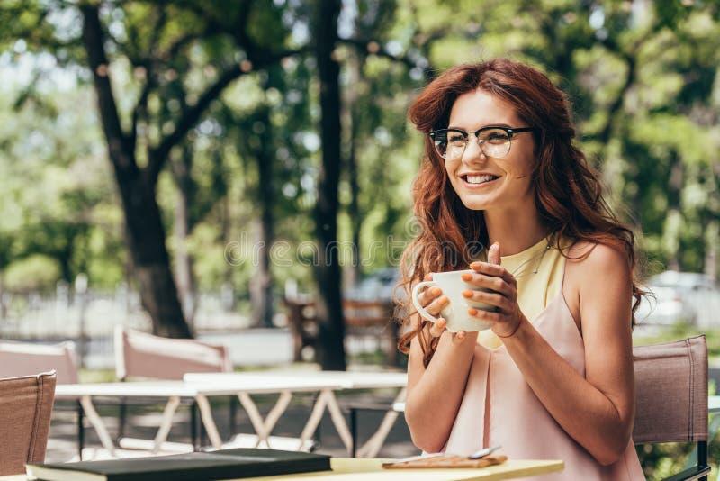 femme d'affaires gaie dans des lunettes avec la tasse de café se reposant à la table avec le carnet image stock