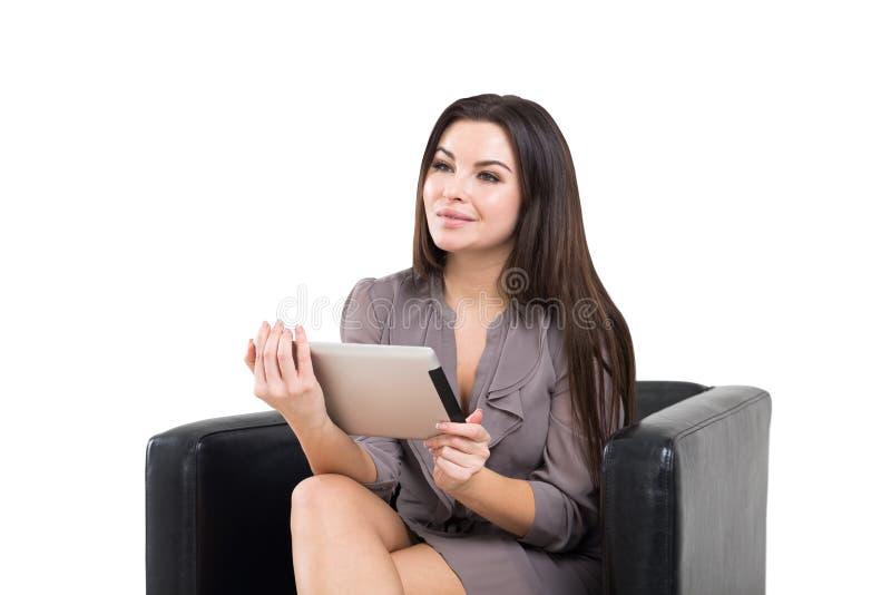 Femme d'affaires gaie dans le fauteuil, un comprimé photo libre de droits