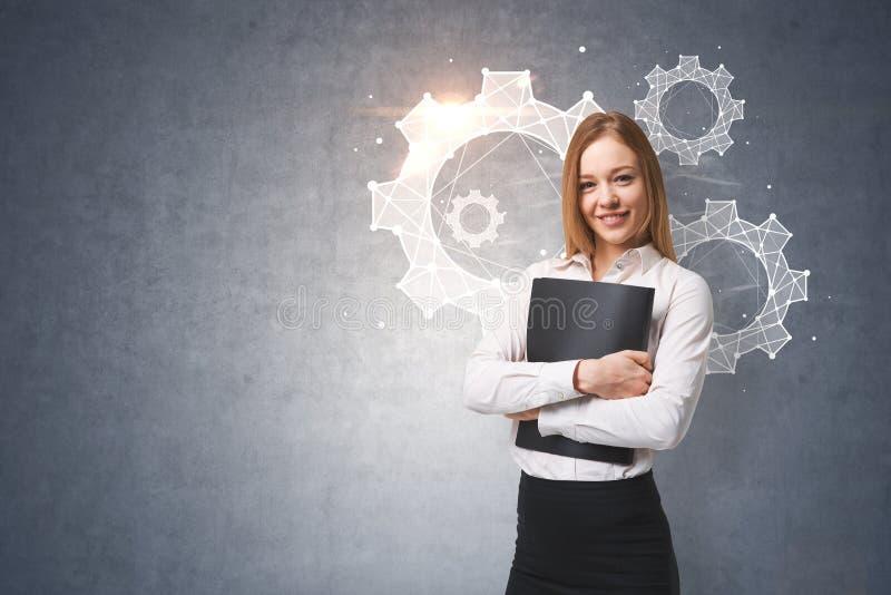 Femme d'affaires gaie, roues dentées, mur gris image stock