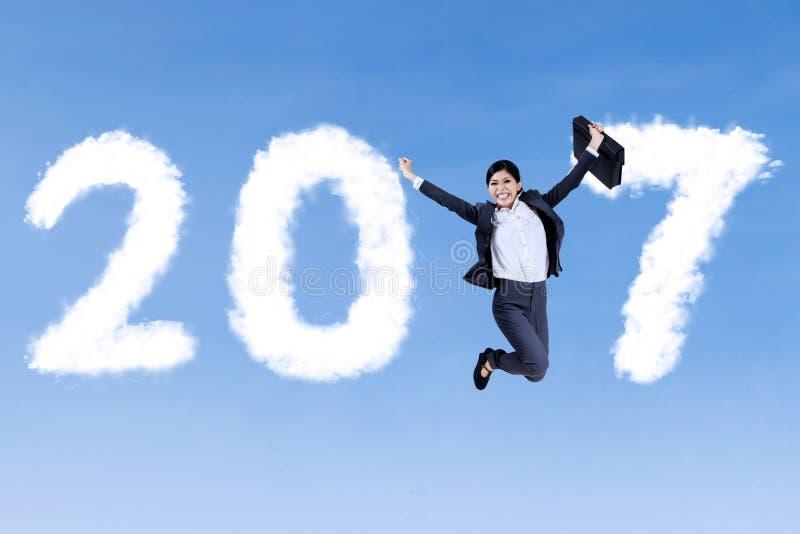 Femme d'affaires gaie sautant avec 2017 images stock