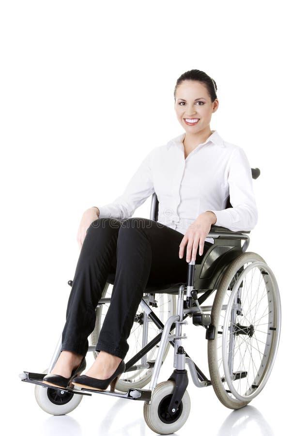 Femme d'affaires handicapée attirante s'asseyant dans un fauteuil roulant images libres de droits
