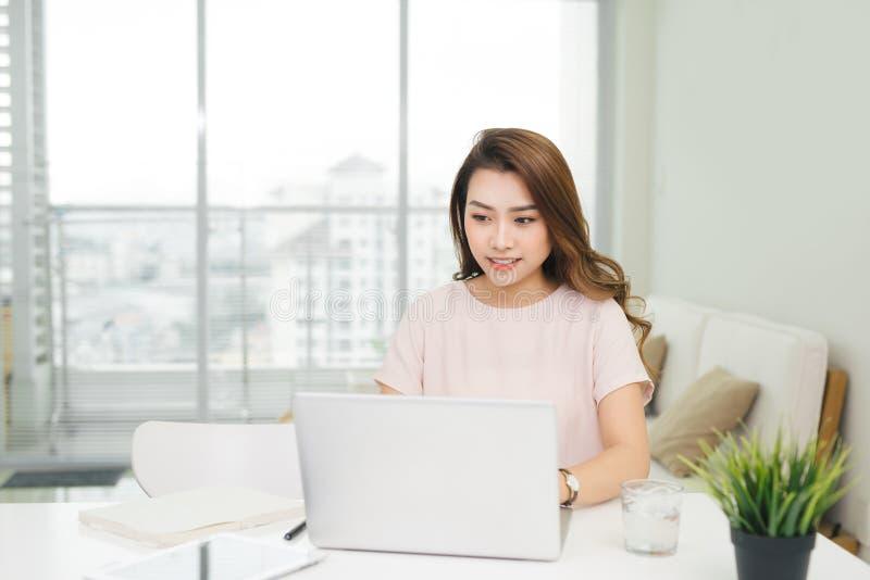 Femme d'affaires heureuse à l'aide de l'ordinateur portable sur le lieu de travail dans le bureau photos stock