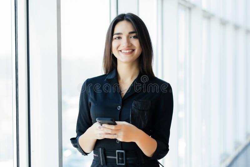Femme d'affaires heureuse à l'aide du smartphone dans le bureau près de la fenêtre photographie stock