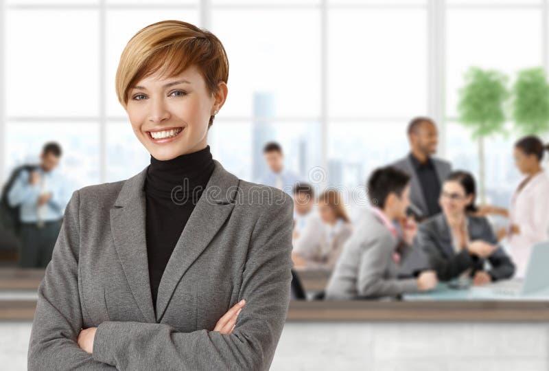 Femme d'affaires heureuse au bureau photographie stock libre de droits