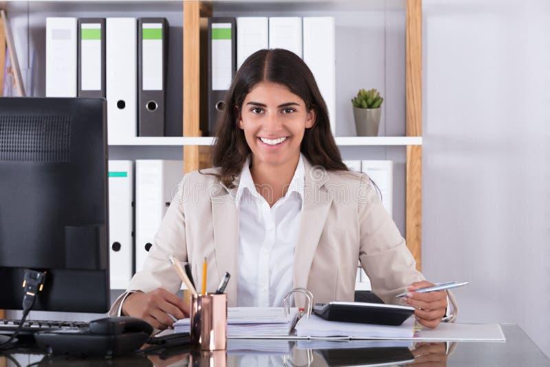 Femme d'affaires heureuse Calculating Financial Data image stock
