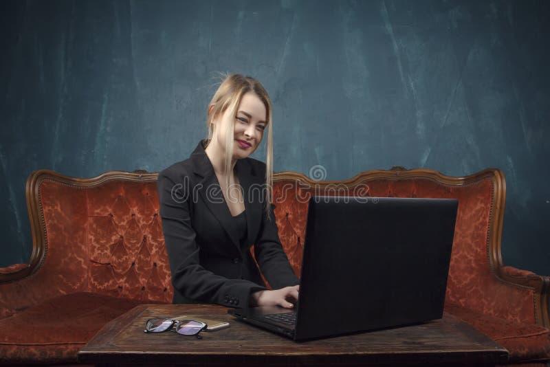 Femme d'affaires, femme heureuse dans le costume souriant utilisant l'ordinateur portable pour le travail dans l'intérieur de vin images stock