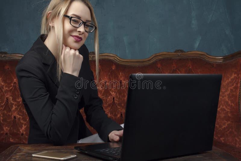 Femme d'affaires, femme heureuse dans le costume souriant utilisant l'ordinateur portable pour le travail dans l'intérieur de vin photo libre de droits