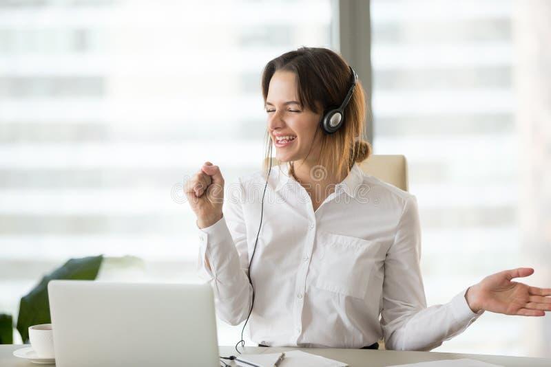 Femme d'affaires heureuse enthousiaste écoutant la musique dans des écouteurs à images stock