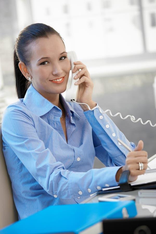 Femme d'affaires heureuse parlant du téléphone photo stock