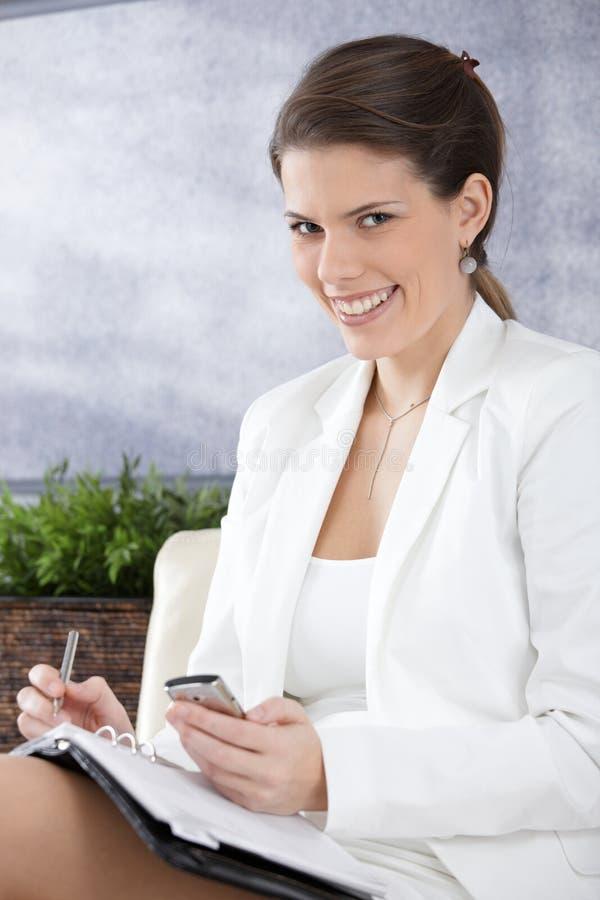 Femme d'affaires heureuse prenant des notes images stock