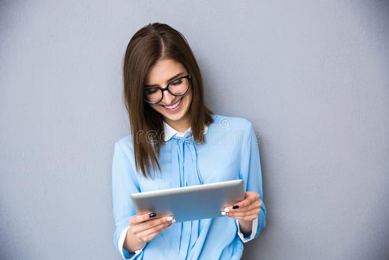 Femme d'affaires heureuse se tenant avec l'ordinateur de table photo stock