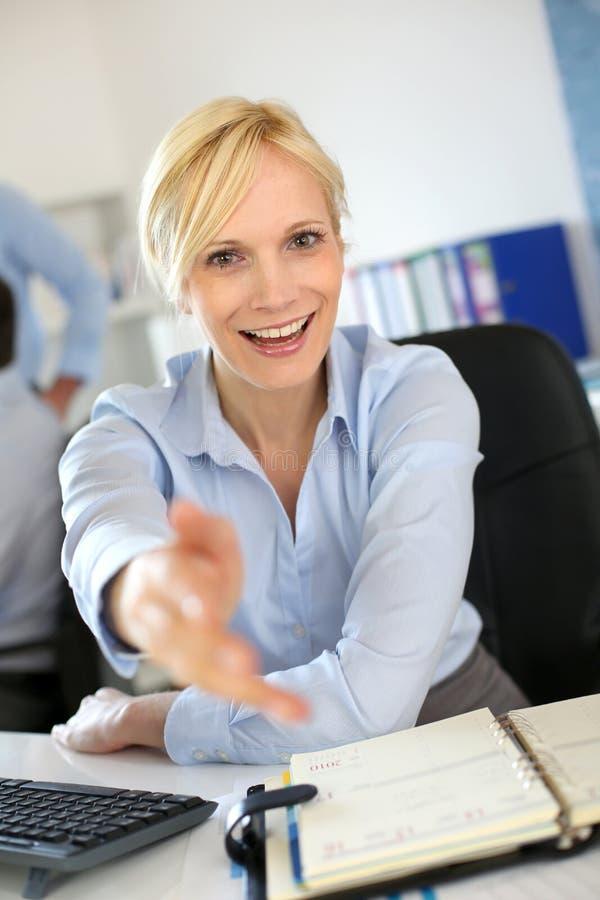 Femme d'affaires heureuse souhaitant la bienvenue au client images stock