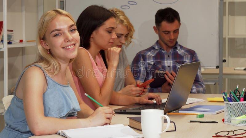 Femme d'affaires heureuse souriant à l'appareil-photo au cours de la réunion photographie stock