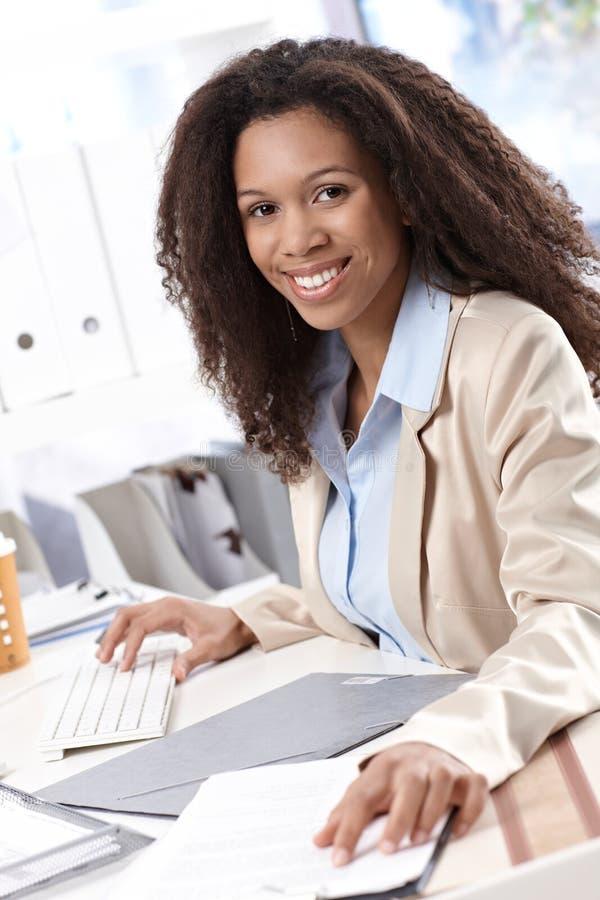 Femme d'affaires heureuse travaillant au bureau images stock