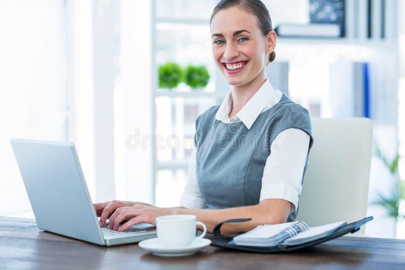 Download Femme D'affaires Heureuse Travaillant Sur L'ordinateur Portable Et Regardant L'appareil-photo Photo stock - Image du femelle, confiant: 56480794