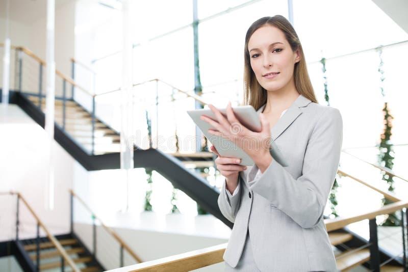 Femme d'affaires Holding Digital Tablet dans le bureau photographie stock