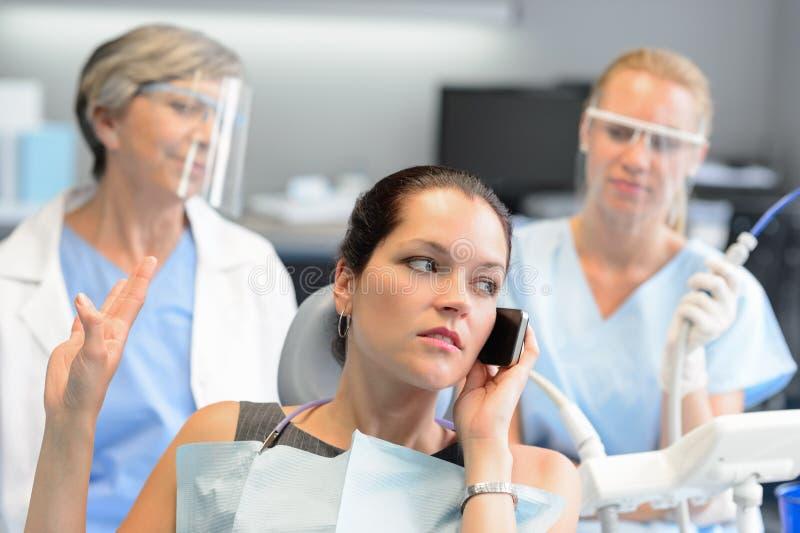 Femme d'affaires impolie au téléphone dans le bureau dentaire photos stock