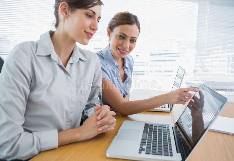 Femme d'affaires indiquant quelque chose sur l'ordinateur portable pour le collègue images stock