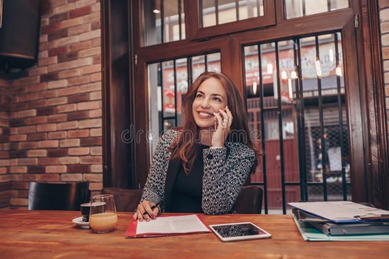 Femme d'affaires invitant le téléphone portable et prenant des notes photos stock