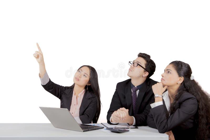 Femme d'affaires japonaise indiquant l'espace vide tandis que d'autres membres de l'équipe prêtent l'attention photo stock