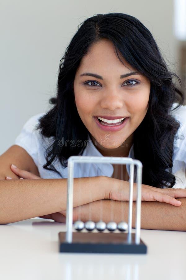 Femme d'affaires jouant avec des billes de Newton photo stock