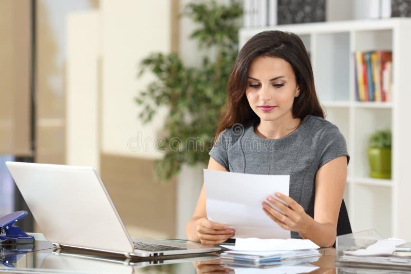 Femme d'affaires lisant une lettre au bureau photographie stock libre de droits