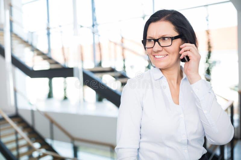 Femme d'affaires Looking Away While employant Smartphone dans le bureau photographie stock
