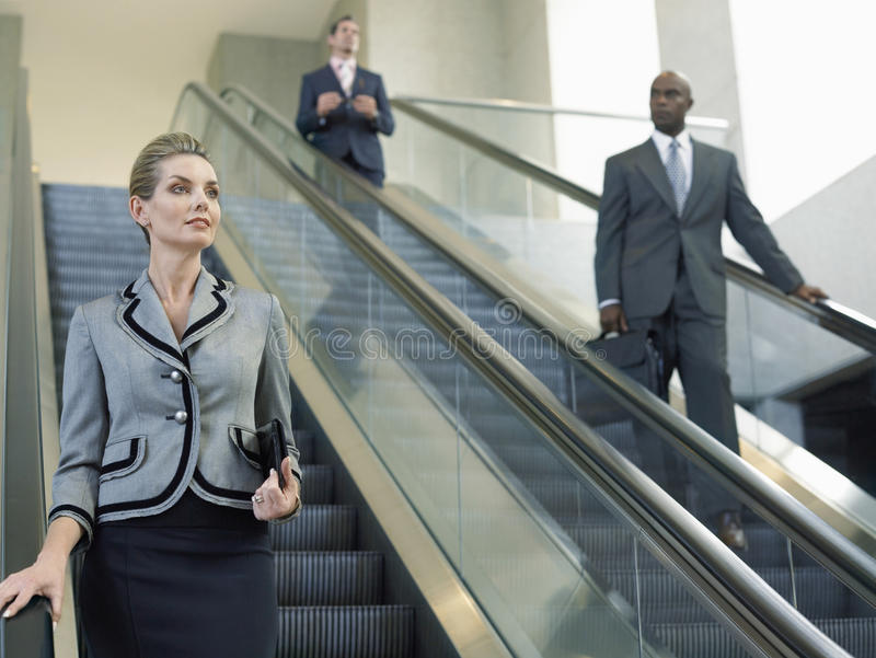 Femme d'affaires Looking Away While se déplaçant vers le bas sur l'escalator image libre de droits