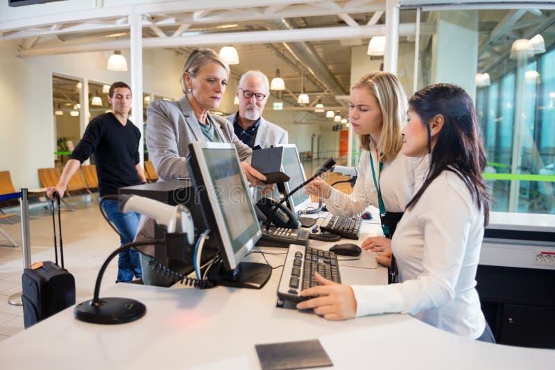 Femme d'affaires Looking At Staff travaillant à l'enregistrement d'aéroport image stock