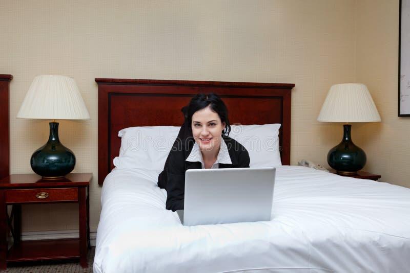 Femme d'affaires Lying sur le lit avec l'ordinateur portable photos stock
