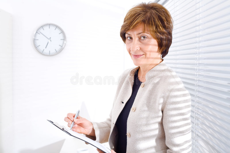 Femme d'affaires mûre au bureau photos libres de droits